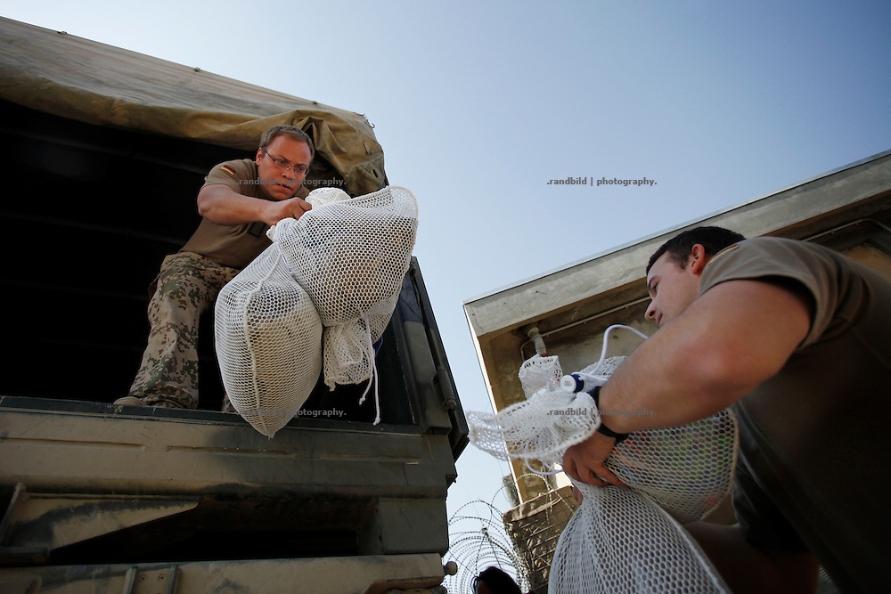 german soldiers unload bags of fresh washed laundry at District Headquarters, Chahar Dareh.