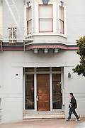 A man walks down a hill in front of a building in San Francisco.