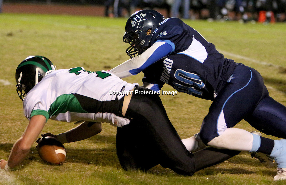Hoggard's Kyle Delaney tackles West Brunswick's Dylan Darguzas as he chases a fumbled ball Monday night at Hoggard High School. (Jason A. Frizzelle)