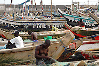 GHANA,Accra,Jamestown, 2007. Fishermen take time at the end of the afternoon to mend their nets. Much of the catch from these small boats is smoked and sold to local markets.