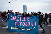 Frankfurt | 25 February 2017<br /> <br /> Am Samstag (25.02.2017) nahmen etwa 1000 Menschen in Frankfurt am Main an einer linksradikalen Demonstration unter dem Motto &quot;Make Racists Afraid Again&quot; Teil. Die Demo begann am S&uuml;dbahnhof in Frankfurt-Sachsenhausen und endete am Willy-Brandt-Platz. Organisiert wurde der Aufmarsch von dem B&uuml;ndnis &quot;Antifa United Frankfurt&quot;.<br /> Hier: Die Demo &uuml;berquert die Fl&ouml;&szlig;er Br&uuml;cke, zwei Demonstrantinnen tragen ein Transparent mit der Aufschrift &quot;Naziler Defolun!&quot; (Nazis verschwindet!). Im Hintergrund ist die EZB (ECB) zu sehen.<br /> <br /> photo &copy; peter-juelich.com