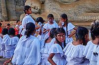 Sri Lanka, province du Centre-Nord, cité historique de Polonnaruwa, classée au Patrimoine Mondial de l'UNESCO, Gal Vihariya (Gal Vihara), ensemble des quatres statues de Bouddha taillées dans la roche, bouddha couché, ecoliers en devotion // Sri Lanka, Ceylon, North Central Province, ancient city of Polonnaruwa, UNESCO World Heritage Site, Gal Vihara, reclining Buddha, scholars