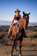 Femaler Horseback rider on horse in the hills above the ocean near Morro Bay, Montana de Oro State Park, California
