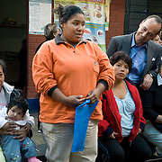 Congressman Luis Gutierrez (D,IL) listens to Lisette, an expecting mother, speak during CARE's Learning Tour visit to the San Cosme Health Center. San Cosme is a slum in Lima that has the highest rate of tuberculosis in Lima, but has limited health services for the community. The Global Fund is supporting services in San Cosme's health center.