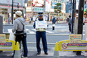Shinbashi Tokyo man in uniform holding a sign up