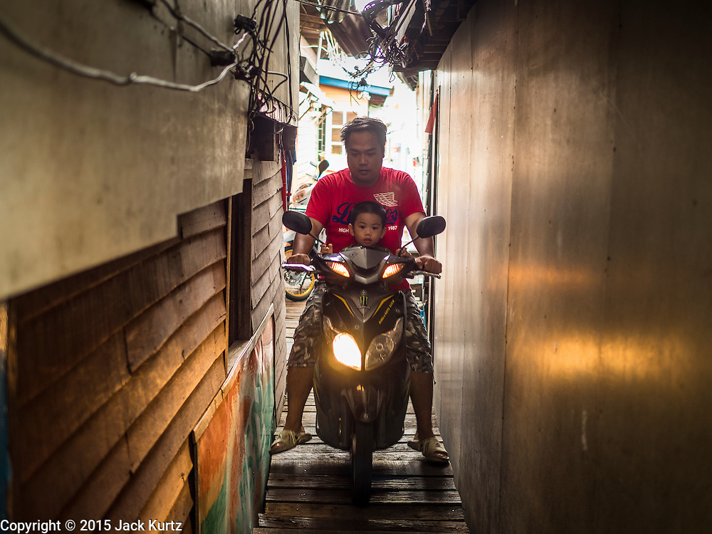 22 JULY 2015 - BANGKOK, THAILAND:    A man and his son on a motorcycle between houses in a community along the Chao Phraya River south of Krung Thon Bridge. This is one of the first parts of the riverbank that is scheduled to be redeveloped. The communities along the river don't know what's going to happen when the redevelopment starts. The Chao Phraya promenade is development project of parks, walkways and recreational areas on the Chao Phraya River between Pin Klao and Phra Nang Klao Bridges. The 14 kilometer long promenade will cost approximately 14 billion Baht (407 million US Dollars). The project involves the forced eviction of more than 200 communities of people who live along the river, a dozen riverfront  temples, several schools, and privately-owned piers on both sides of the Chao Phraya River. Construction is scheduled on the project is scheduled to start in early 2016. There has been very little public input on the planned redevelopment.           PHOTO BY JACK KURTZ