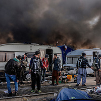 26th October 2016, The Jungle of Calais in France is in huge fire. Afghan migrants next to they caravan. Some of them cooking their lunch and some of them are leaving the camp.