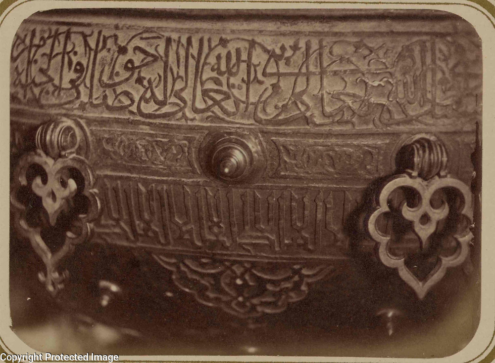 1868<br /> This photograph of a detail of a ritual basin in the interior of the mausoleum of Khodzha Akhmed Iassavi in Yasi (present-day Turkestan, Kazakhstan) is from the archeological part of Turkestan Album. The six-volume photographic survey was produced in 1871-72 under the patronage of General Konstantin P. von Kaufman, the first governor-general (1867-82) of Turkestan, as the Russian Empire&rsquo;s Central Asian territories were called. Yasi is associated with the Sufi mystic, Khodzha Akhmed Iassavi (1103-66), whose great reputation led Timur (Tamerlane) to construct a memorial shrine (khanaka) at his grave site. Built in 1396-98, the mausoleum displays features of Timurid architecture, then at its height in Samarkand. This view shows part of a large bronze ritual water basin, stated by an inscription on the basin to have been donated by Timur. The basin is elaborately decorated with botanical figures and Perso-Arabic inscriptions. At the top is the beginning of a band of Naskh script intertwined with a tendril pattern. Below this band are decorative bronze fittings and two more inscription bands, in block letters. On the curved surface at the bottom of the photograph is an arabesque figure. The height of the basin is about one meter.
