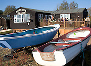 Dinghies on the shore with riverside tearoom, Orford, Suffolk, England