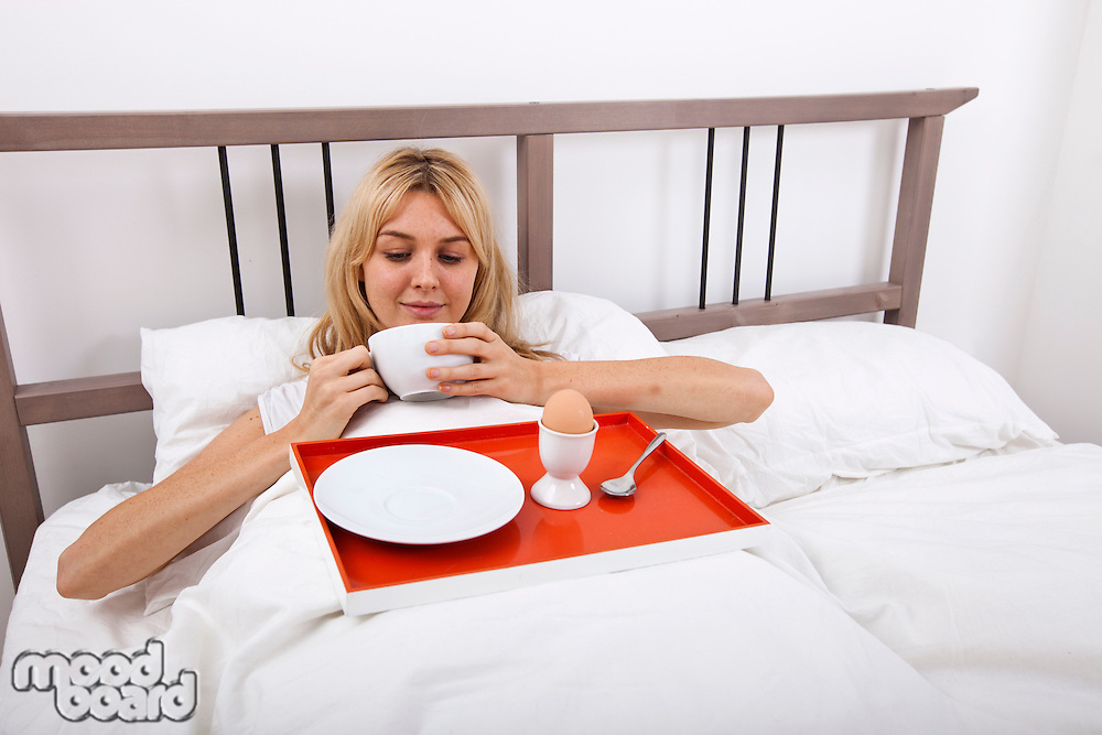 Young woman with breakfast tray in bed
