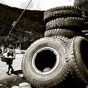 UN NI&mdash;O PASA ANTE UN TALLER DE REPARACION DE   NEUMATICOS EN LA &quot;TRANCA&quot; (CONTROL POLICIAL)<br />  DE YOLOSA.CARRETRA DE LOS YUNGAS. BOLIVIA.<br /> FOTO : JORDI CAMI