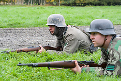 Re-enactors portrayiing German panzer grenadiers from the Großdeutschland Division. both are wearing the iconic Steel Helmet. The man on the left has a gefreiter rank badge on his arm. The soldier on the right is wearing a tactical rank badge of Feldwebel on his camouflage smock<br />