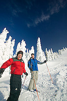 snow encrusted trees and a fresh dump of snow at Mount Washington make for a great day of skiing for two mature adults.  Mount Washington, Comox Valley, Vancouver Island, British Columbia, Canada.