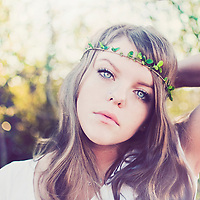 Close up of young woman with blonde hair blue eyes outdoors wearing a leaf headband