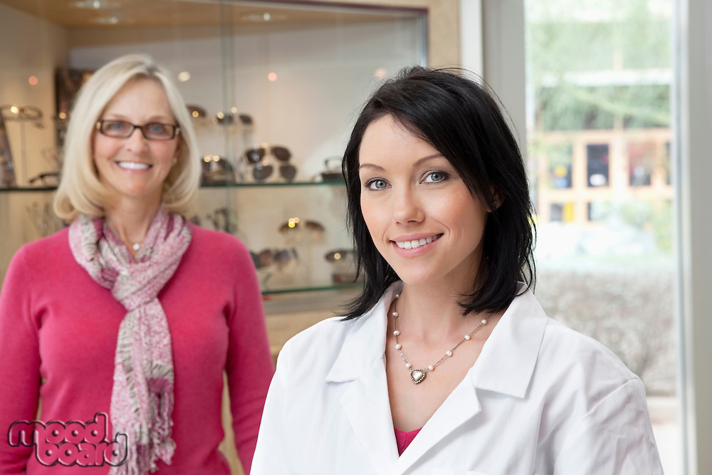 Portrait of a mid adult optometrist with female wearing glasses in background