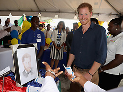 Prince Harry is presented with a portrait on Grand Anse Beach as he visits Mangrove restoration projects ahead of visiting the coral reef in Grenada during the second leg of his Caribbean tour.