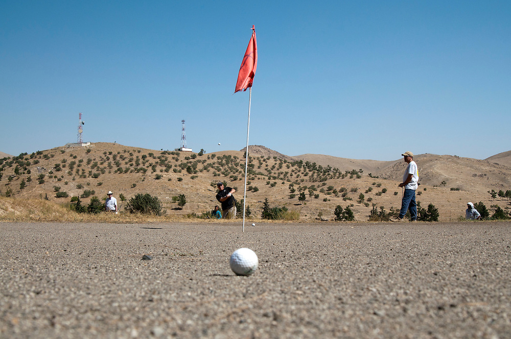 """Golfers enjoy the outdoors and the opportunity to escape the city at the Kabul Golf Club, Kabul, Afghanistan.  The nine hole (18 holes if played in reverse) par 36 course is 5,522 yards of hard packed desert sand, scrub brush, ants, and persistent thorns.  The course has no grass. The greens are """"browns,"""" made from sand saturated with motor oil to keep them from blowing away."""