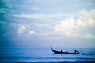 Silhouette of fishermen in a Moken boat near Kata Noi beach, Phuket, Thailand.