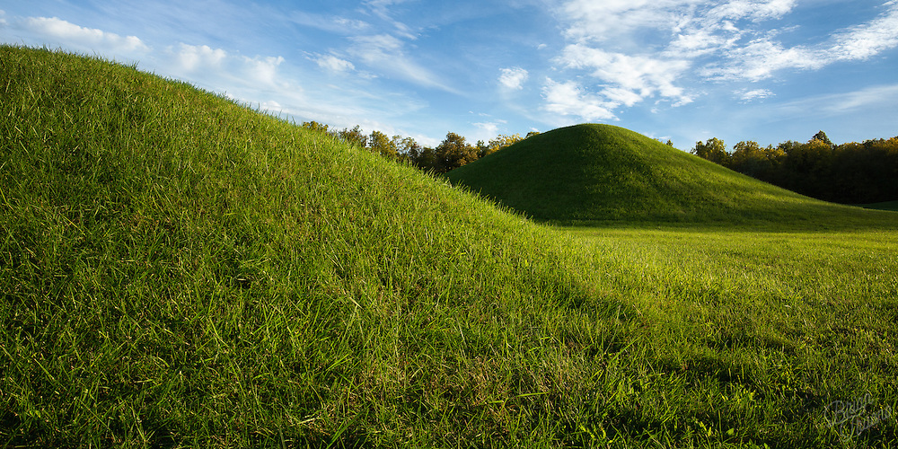 Elaborate earthworks scatter the Ohio countryside, built an estimated two thousand years ago by unknown tribes of Native Americans. Many of the mounds were hundreds of feet long, and several stories tall. Some of these mound groups were expertly laid out in shapes that often mimicked celestial coordinates. Though the official name of the ancient peoples has been lost to time, the given name &ldquo;Hopewell&rdquo; comes from Capt. Mordecai Hopewell, the farmer who owned some land where part of the mound cities were discovery. It&rsquo;s thought that the Hopewell people utilized these plots of land for ceremonial, public spaces, coordinating celestial events, or as burial grounds.<br /> <br /> The mounds were constructed with careful layering of alternating clays, sand, and soil, which indicate that there was much thought in the process of creation. Beneath those layers, archaeologists discovered post holes in a plastered clay floor, believed to have been to hold the walls of a building or structure. It seems that the buildings were deconstructed and mounds were laid in their place after their purpose was served. Large amounts of artifacts were found buried in the collected earth, most of them were intricate works of art used for ceremonial purpose such as statues, effigies, and pottery. There was little indication of people living amongst the mound cities but there was evidence of hundreds of cremated remains. Perhaps it was all a way to celebrate the lives of the people who live here before.