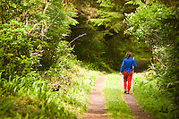 A young hiker strolls along a path towards the Ronning Garden, a remote oasis of unique flora and fauna near the main logging road that eventually leads to Cape Scott on Northern Vancouver Island. Ronning Garden, Holberg, Northern Vancouver Island, British Columbia, Canada.