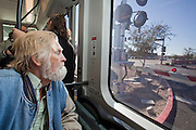 28 DECEMBER 2008 -- PHOENIX, AZ: A passenger looks out the window as the new Metro light rail train goes over a street crossing in Tempe, AZ. The new Metro Light Rail is 20 miles long and cost $1.4 billion dollars. Construction was funded by local, state and federal monies. The trains will operate on one line through Phoenix and the suburban communities of Tempe and Mesa. The trains started running Saturday, Dec 27, 2008 and will be free until Jan. 1, 2009. The regular fare will be $1.25 for one ride or $2.50 for an all day pass.  Photo by Jack Kurtz / ZUMA Press
