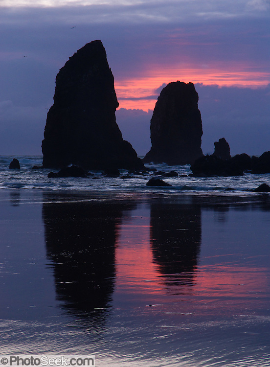 The pounding Pacific Ocean has eroded these sea stack rocks from bluffs at Cannon Beach, Oregon, USA. The glowing ball of sun glows yellow orange.