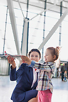 Portrait of airport staff holding airplane toy while playing with cute little girl in airport
