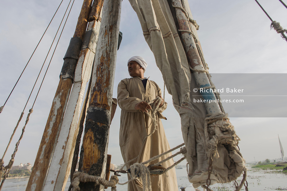 A crewman of a felucca looks over to the riverbank while sailing his boat on the River Nile at Luxor, Nile Valley, Egypt. Feluccas are ancient Egyptian sail boats which were used in ancient times as a primary mode of transport and are the only type of boat that is still used extensively in the country.