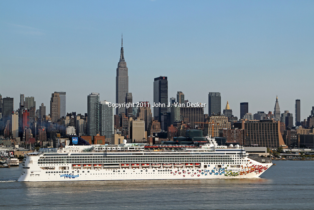 The Cruise Ship, Norwegian Gem, steaming down the Hudson River past Mid-town Manhattan and beginning its journey. New York City, New York, USA