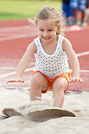 Middletown, New York - A young girl lands in the long jump pit during the Twilight Track and Field Series run by the Middletown High School Varsity track program on July 22, 2014.