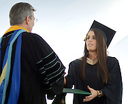 Delaware Valley University President Dr. Joseph S. Brosnan (L) hands a Master of Business Administration Degree to Jenna V. Chwal during commencement ceremonies Saturday May 16, 2015 at Delaware Valley University in Doylestown, Pennsylvania. This is the first class to graduate from Delaware Valley University. (Photo by William Thomas Cain/Cain Images)