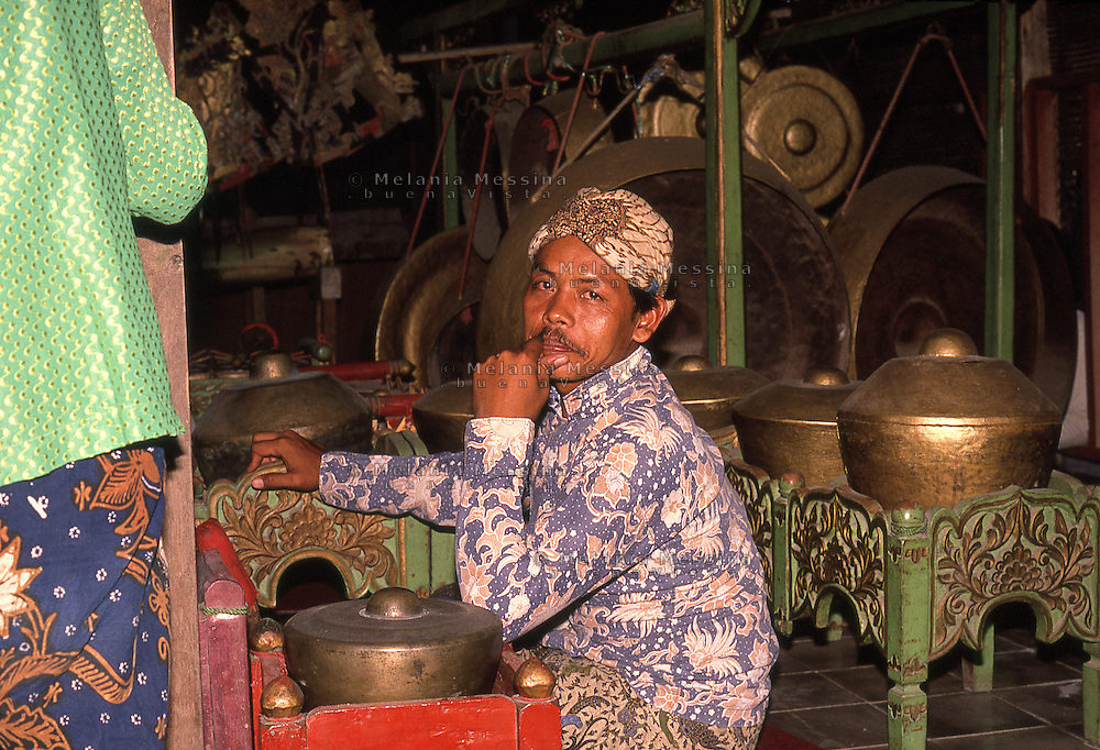 traditional gamelan orchestra musician playing during wayang kulit performance.<br /> musicista della  gamelan orchestra accompagna lo spettacolo del teatro delle ombre (wayang kulit)