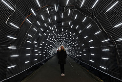 "© Licensed to London News Pictures. 22/11/2018. LONDON, UK. A visitor stands in a tunnel of lights. Preview of the first ""Christmas at London Zoo"", a festive transformation at ZSL London Zoo which features a one-mile illuminated pathway in a magical after-dark experience.  Historic buildings have been transformed for the event, with glowing fountains lighting the Grade I listed Lubetkin Penguin Pool and festive projections lighting up the historic Mappin Terraces.  The show runs 22 November to 1 January 2019.  Photo credit: Stephen Chung/LNP"