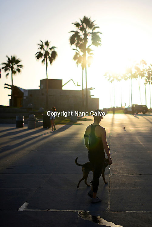 Young woman with dog at sunset, Venice Beach, California.