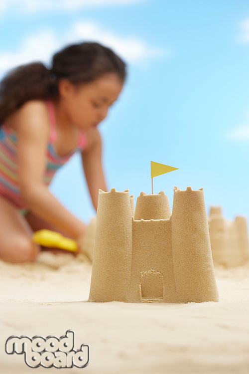 Girl (7-9 years) building sand castles on beach focus on sand castle in foreground