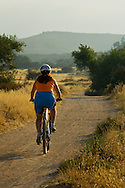 Mountain biker on dirt trail through the Los Penasquitos Canyon Preserve, San Diego, California
