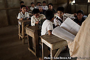 A teacher recites a passage from a Lao language book while his students follow along at The Ban Buamlao Primary School in Ban Buamlao, Laos. The boys sit on one side of class while the girls choose to be adjacent to open windows on this day at the rural schoolhouse.
