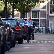 Prins Maurits krijgt een shirt van Oger thuisbezorgd, telefonerend, door koerier op fiets
