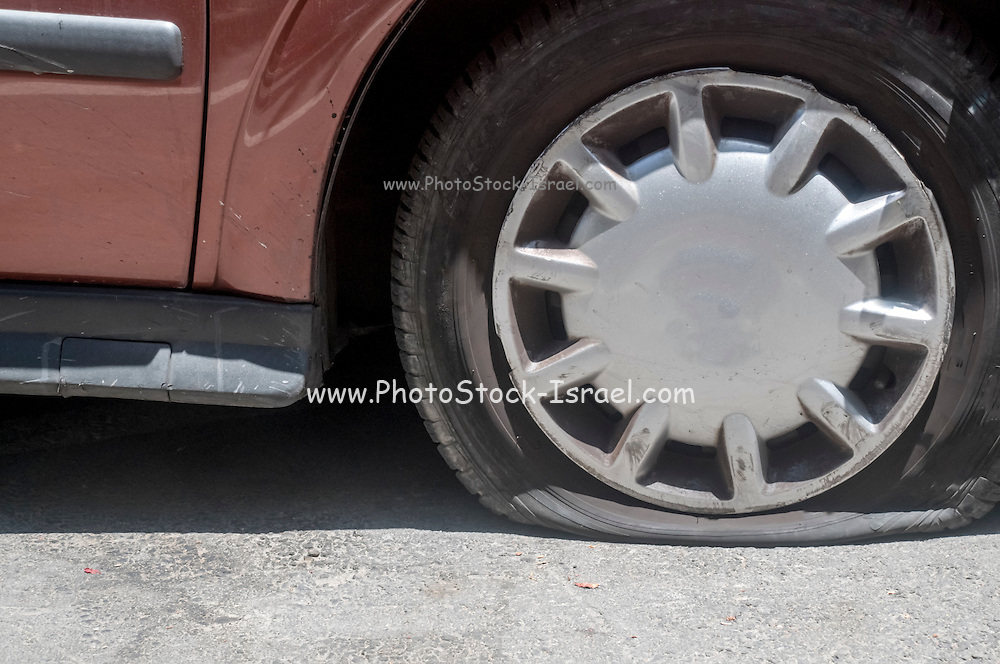 A vandalised car, two punctured tires and scratche along the side of the car and on the hood