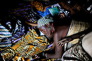 A traditional birth attendant is listening at the belly of a young, 8-months-old pregnant woman in Mataska village near Port Loko, Sierra Leone. it is her first pregnancy and she has never seen a doctor. Traditional birth attendants often send the women to the hospital only, if labour goes on for more than 3 days.