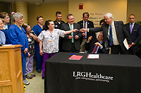 Linda Powell is given the pen by NH Senate Majority Leader Jeb Bradley following the bill signing of HB 1791 by Governor Chris Sununu Thursday morning at Lakes Region General Hospital.  (Karen Bobotas/for the Laconia Daily Sun)