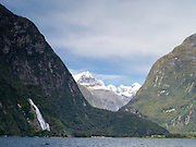 View from the water of Milford Sound, Bowen Falls and Sheerdown Peak, with Mitre Peak Lodge on the lower left and the harbor lower center; Fiordland National Park, New Zealand