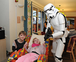 Star Wars, Rachel House, Kinross, 11-12-2016<br /> <br /> People dressed as Star Wars characters to visit children's hospice. Edinburgh 's Capital Sci-Fi Con organiser Keith Armour and other delegates to don costumes and visit children and their families at Rachel House.<br /> <br /> Shannon and her sister, Erin get protected by a Storm Trooper<br /> <br /> (c) David Wardle | Edinburgh Elite media