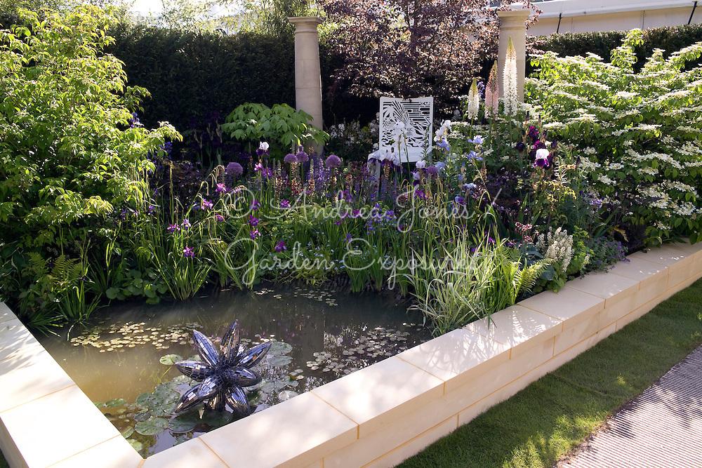 Urban garden with pond, prismatic sculpture 'Rocket Pollen' by Rebecca Newnham, flowering perennial bed including Allium 'Beau Regard', Verbascum 'Helen Johnson', Eremurus, Iris 'Superstition', Iris 'White City', Iris chrysogrpahes, Iris sibirica 'Tropic Night' &amp; Iris 'Jane Philips' &amp; Salvia 'Rhapsody in Blue'. Ornamental trees include Fagus sylvatica Rohanii, Kalopanax &amp; Viburunum plicatum Mariesii, Cornus kousa &amp; Viburnum plicatum Mariesii. Metal chair &amp; stone classical columns.<br /> Dawn Chorus sponsored by Bradstone.Design by Chris Beardshaw. The Chris Beardshaw Mentoring Scholarship Team. Silver-Gilt Flora medal winner