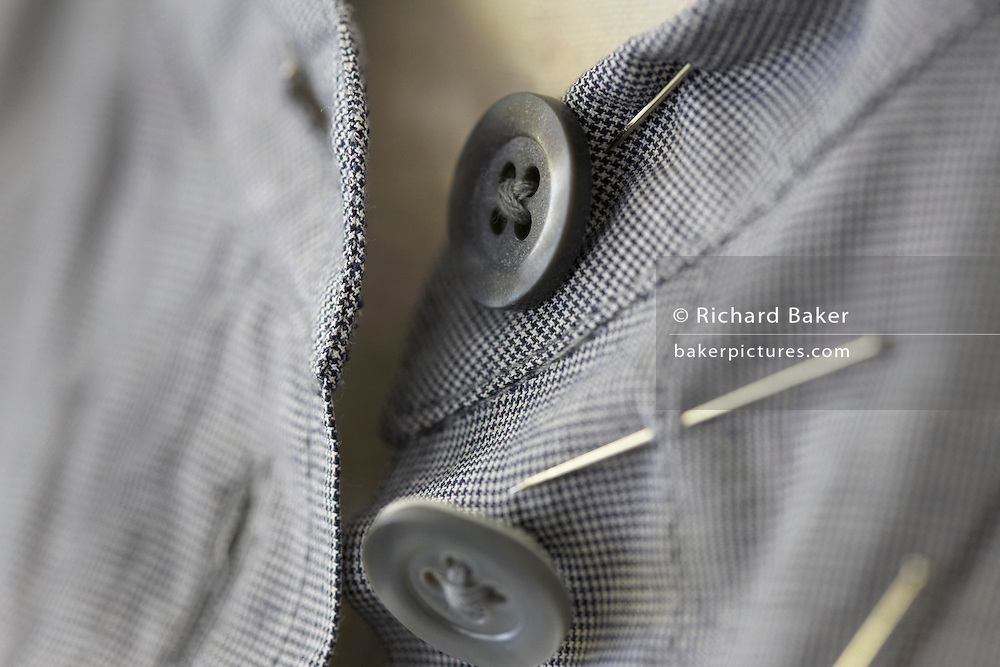 """A detail showing the fine stitching of a cotton dress by couturier Margaret Howell in the company's workshop factory in Edmonton, North London. England. In close-up, the eye is drawn into the centre of focus where the buttons are held in a criss-cross stich in its four holes. There are pins in this still prototype design as it evolves from an idea on paper to an actual garment. The fine check pattern of its fabric is beautifully sewn together in this fine and intricate dress. Howell is one of Britain's more understated of couture brands alongside more flamboyant personalities. Howell admits to being """"inspired by the methods by which something is made .. enjoying the tactile quality of natural fabrics such as tweeds, linen and cotton in a relaxed, natural and lived in look."""""""