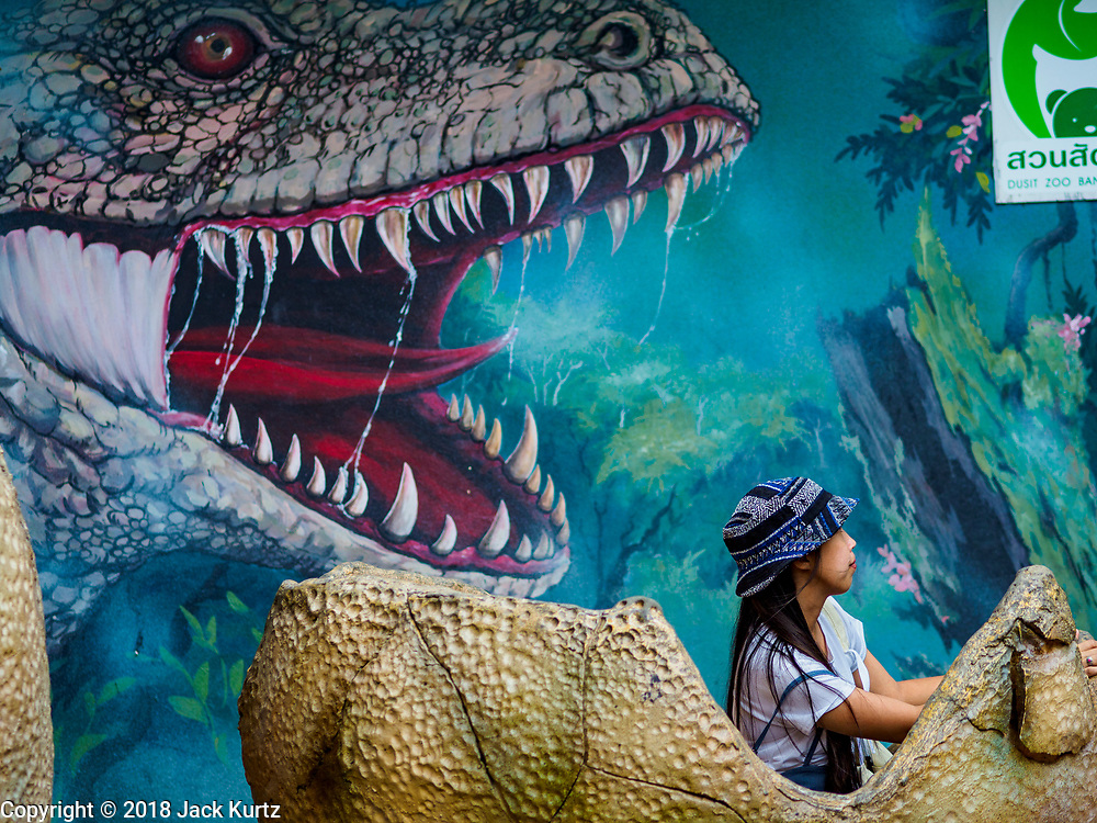 17 AUGUST 2018 - BANGKOK, THAILAND:   A woman sits in what is supposed to represent a dinosaur egg at Dusit Zoo in Bangkok. The zoo opened in 1938. The zoo grounds were originally the Dusit Royal Garden. The zoo is scheduled to close by the end of August 2018 because it is being relocated to Nakhon Pathom province, south of Bangkok.     PHOTO BY JACK KURTZ