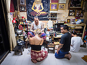 "27 MAY 2015 - BANGKOK, THAILAND: AJARN NENG ONNUT, gives a sacred Sak Yant tattoo to EMILY, a visitor to Thailand from the United Kingdom. Sak Yant (Thai for ""tattoos of mystical drawings"" sak=tattoo, yantra=mystical drawing) tattoos are popular throughout Thailand, Cambodia, Laos and Myanmar. The tattoos are believed to impart magical powers to the people who have them. People get the tattoos to address specific needs. For example, a business person would get a tattoo to make his business successful, and a soldier would get a tattoo to help him in battle. The tattoos are blessed by monks or people who have magical powers. Ajarn Neng, a revered tattoo master in Bangkok, uses stainless steel needles to tattoo, other tattoo masters use bamboo needles. The tattoos are growing in popularity with tourists, but Thai religious leaders try to discourage tattoo masters from giving tourists tattoos for ornamental reasons.     PHOTO BY JACK KURTZ"