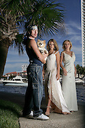 Fashion designer Sebastian Toulouse with two of his best clients Britten Simon and her mother Michelle Simon wearing the gowns he designs. Toulouse is holding the Simon's dog Virgo near the Simon home in Adventura.