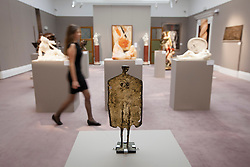 © Licensed to London News Pictures. 08/11/2013. London, UK. A Sotheby's employee walks past 'Flat Standing Figure' (1952) (est. GB£18,000-25,000) by British sculptor Kenneth Armitage, one of 285 pieces of art that make up Sotheby's latest sale 'Defining Taste' at the London based auction houses New Bond Street premises. The auction, set to take place on the 12th of November 2013, consists of art, ranging in price from GB£100-120,000 and from the middle ages to very present works, that were collected during the 45 year career of esteemed art dealer Danny Katz. Photo credit: Matt Cetti-Roberts/LNP