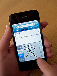 Student using app to learn mandarin Chinese characters on an Apple iphone 4G smartphone